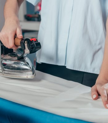cropped shot of female dry cleaning worker using industrial iron