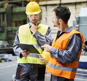 two-men-wearing-protective-workwear-holding-clipboard-and-talking-in-factory-BSZF00591